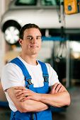 stock photo of auto repair shop  - Auto mechanic standing in his workshop in front of a car on a hoist - JPG