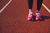 Постер, плакат: Woman Legs In Sportswear And Running Shoes Standing On Running Track