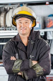 foto of firemen  - Portrait of happy mature fireman standing arms crossed at fire station - JPG