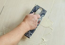 foto of grout  - The hand of man holding a rubber float and filling joints with grout - JPG