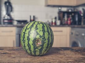foto of bruises  - A bruised and rotten watermelon on a table in a kitchen - JPG