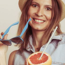 pic of flirty  - Happy glad woman tourist in straw hat holding sunglasses and grapefruit citrus fruit - JPG
