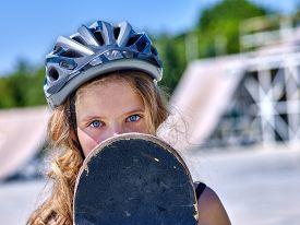 stock photo of skateboard  - Face of teen skateboarding his skateboard outdoor - JPG