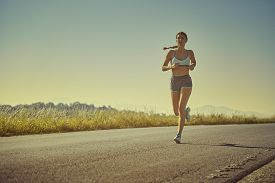 picture of sportswear  - Active sporty woman in summer sportswear running sprinting on a road at sunrise or sunset - JPG
