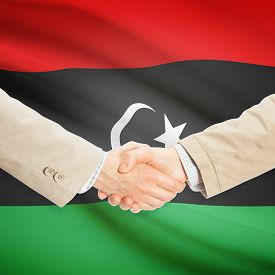 picture of libya  - Businessmen shaking hands with flag on background  - JPG