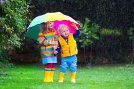 foto of rainy weather  - Little girl and boy with colorful umbrella playing in the rain - JPG