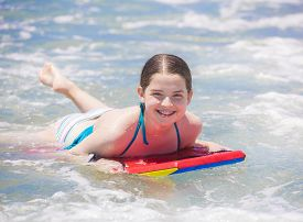 foto of boogie board  - Cute young teenager smiling with braces while on a boogie board and playing in the ocean waves - JPG