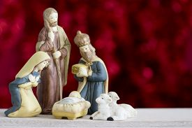 picture of baby sheep  - Nativity Scene with Baby Jesus Mary Joseph Sheep and a Wise Man on a Red Background with Copy Space - JPG