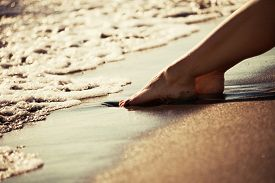 stock photo of barefoot  - woman barefoot legs on sand beach by the sea at sunset - JPG