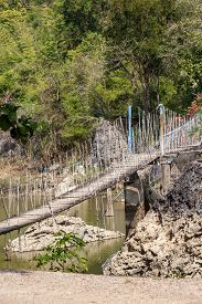 picture of suspension  - above the water between two rocks hangs a suspension bridge - JPG