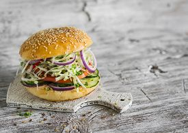 picture of veggie burger  - delicious veggie burger with cabbage tomato cucumber onions and peppers on a light wooden surface - JPG