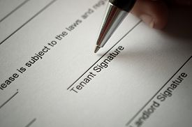 pic of rental agreement  - Rental agreement form with signing hand and pen - JPG