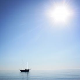pic of sailing vessels  - Sailing ship profile. Toned image. Sunbeams on the sea surface. Morning sea with boat on the horizon. Aged photo. Calm Sea with a Sailing Vessel. Cirali Antalya Province Turkey. ** Note: Soft Focus at 100%, best at smaller sizes - JPG