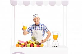 foto of jerks  - Mature soda jerk posing behind a stand full of fresh fruits and holding a glass of orange juice isolated on white background - JPG