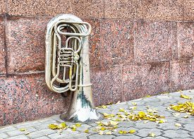 stock photo of wind instrument  - Wind musical instrument outdoor near a granite wall - JPG