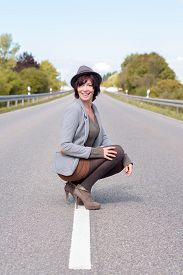 foto of stiletto  - Jaunty trendy young woman crouching on the centre white line on a rural road in her stilettos and hat smiling happily at the camera - JPG