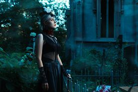 stock photo of wraith  - Woman stands in a cemetery at night - JPG
