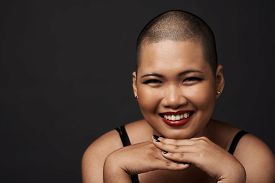 stock photo of shaved head  - Portrait of laughing shaved woman - JPG