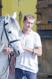 picture of horse-riders  - portrait of a young horse rider and his horse at the byre  - JPG