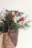 Hand Holding Wildflowers In Wicker Bag At Rustic Window. Colorful Flowers In Brown Basket In Sunligh poster