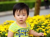 a cute baby is playing in garden