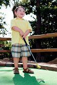 Rapaz joga golfe mini curso de putt putt.
