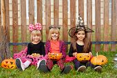 Youthful girls in halloween costumes sitting on grass by fence and eating treats poster