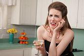 image of sob  - Caucasian woman with a martini in her kitchen sobs - JPG