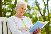 old age, retirement and people concept - happy senior woman reading book sitting on bench at summer  poster