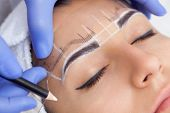Постер, плакат: Permanent Make up For Eyebrows Of Beautiful Woman With Thick Brows In Beauty Salon Closeup Beautici