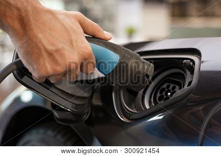poster of Closeup of man hand installing power cable supply for charging electric car. Man hand plugging in po