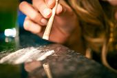 Young woman snorting cocaine with a bill, close-up