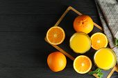 Cutting Board With Orange Juice, Mint And Oranges And Kitchen Towel On Wooden Background, Top View A poster