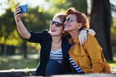 Mature Mother And Adult Daughter Taking Selfie In The Park poster