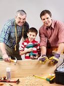 Vertical shot of three multigenerational guys working in a woodshop and smiling at camera poster