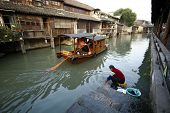 WUZHEN, CHINA - NOVEMBER 25: Tourists in a paddle boat watch a local lady wash her clothes the tradi