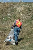 picture of pick up  - A man wearing a reflective vest picking up spring garbage - JPG