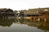 WUZHEN, CHINA - NOVEMBER 25: Tourists visit the wooden houses along the canal of this 1300 years old water town observing traditional craftsmen and local events on November 25, 2011 in Wuzhen, China.