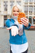 A Young Beautiful Tourist Woman Holds A Traditional Belgian Waffle In One Hand And Invites You To Co poster