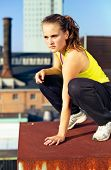stock photo of parkour  - Young woman traceur balanced on the edge of a high building taking stock of her immediate environment before beginning parkour - JPG