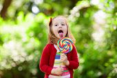 Cute Little Girl With Big Colorful Lollipop. Child Eating Sweet Candy Bar. Sweets For Young Kids. Su poster