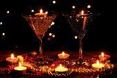 Asombrosa composición de velas y copas en la mesa de madera en fondo claro
