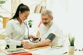 The Visiting Nurse Or Health Visitor Taking Care Of Senior Man. Lifestyle Portrait At Home. Medicine poster