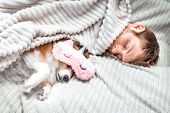 Red Dog Sleeps In A Pink Sleeping Mask With His Owner In The Bed. Concept Weekend And Vacation poster