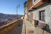 Narrow stone paved street and old houses in town of La Morra, Northern Italy.