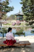 foto of hanbok  - A Korean woman in traditional dress called a Hanbok sits on a bench admiring the view at Kyoungbok Palace in Seoul Korea - JPG