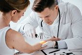Selective Focus Of Dermatologist Examining Hand Of Woman With Dermatoscope poster