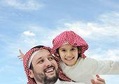 Arábia saudito pai e seu filho pequeno em ombros