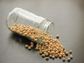 Dried Cheakpea Beans Are Poured From A Glass Jar On Brown Wooden Surface. Cheakpea Beans  In A Glass poster