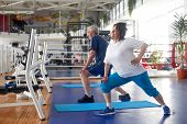 Active Couple Of Seniors Exercising At Gym. Sportive Happy Elderly Woman Performing Exercise In A Fi poster